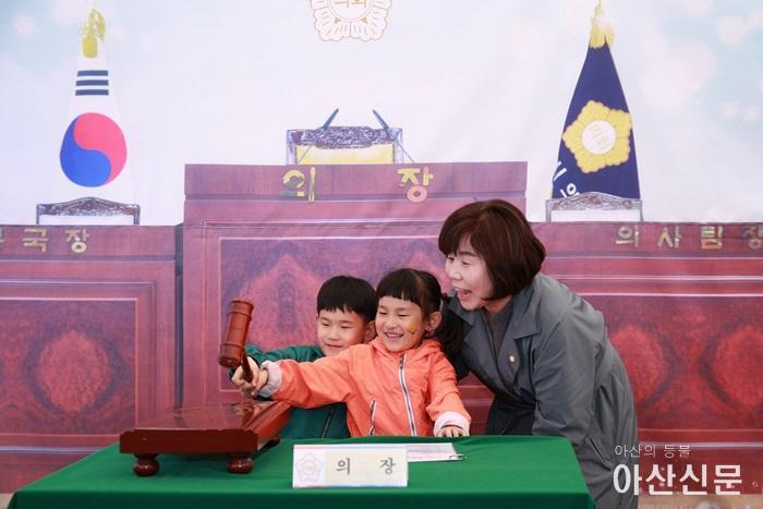 아산시의회 김영애 의장이 어린이들에게 의회기능 설명과 함께 의사봉 3타 치는 장면을 설명하고 있다.JPG