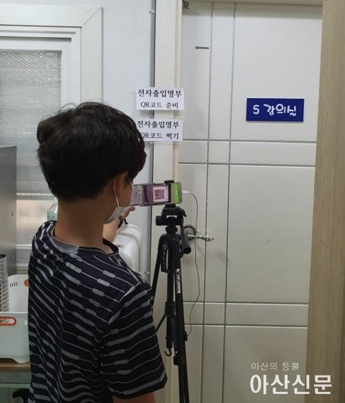 QR코드를 생성하여 학원에 입장하고 있는 학생 사진.jpg